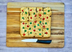 holiday m&m bars cut up on a wooden cutting board