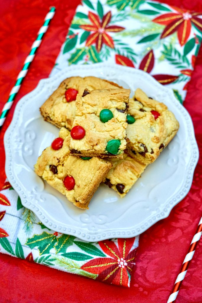 m&m christmas cookie bars on a white plate with festive napkin backdrop