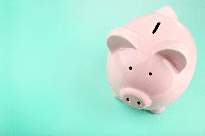pink piggy bank on light teal background